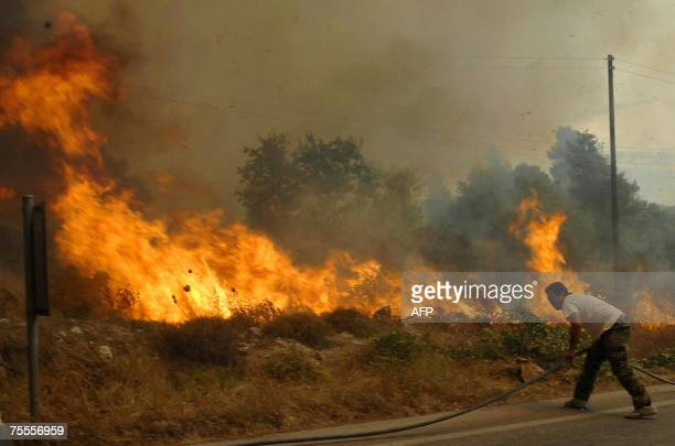A local resident helps firemen battle a forest fire in Corinth west of Athens 19 July 2007 A children's summer camp in southern Greece and an entire...