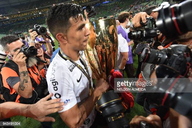 Corinthians player Balbuena holds the trophy after his team won the 2018 Paulista championship final football match against Palmeiras held at Allianz...