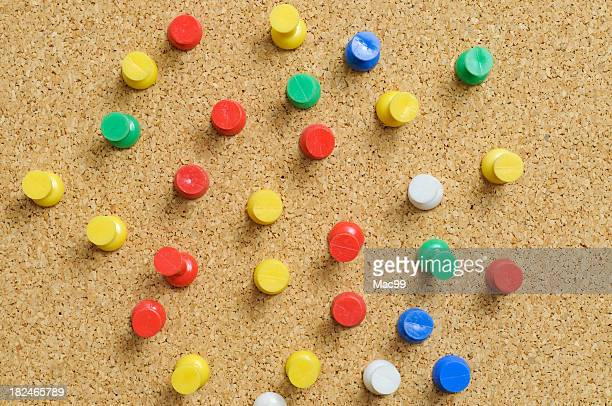 Cork board with red yellow green and white drawing pins