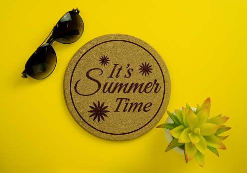 Cork Board with the Phrase 'It's Summer Time' with Sunglasses and Potted Plant on Yellow Background. 955569180