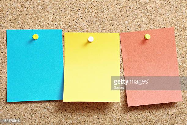 A cork board with three post it notes in blue yellow and red