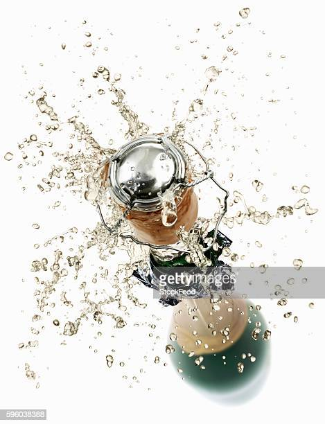 cork flying out of a sparkling wine bottle - champagne cork stock photos and pictures