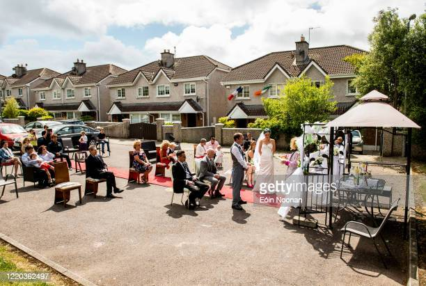 Cork Ireland 16 June 2020 Family and neighbours watch the ceremony of Terence Lenihan and Tara Leguilloux during their COVID19 wedding at their home...