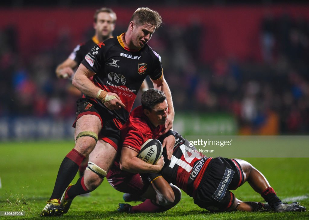 Cork , Ireland - 3 November 2017; Ian Keatley of Munster is tackled by Aaron Wainwright, left and Ashton Hewitt of Dragons during the Guinness PRO14 Round 8 match between Munster and Dragons at Irish Independent Park in Cork.