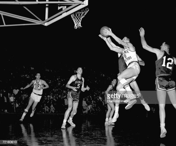 Corky Devlin of the Fort Wayne Zollner Pistons tries to score as Chuck Share and Jack Coleman of the St Louis Hawks wait for any rebound during a...