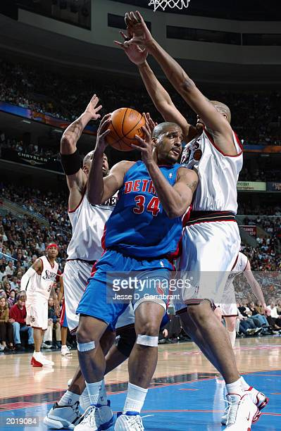 Corliss Williamson of the Detroit Pistons looks to pass while defended by Derrick Coleman of the Philadelphia 76ers in Game six of the Eastern...