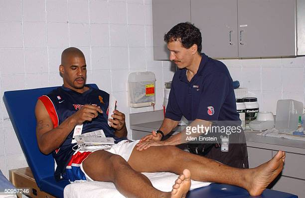 Corliss Williamson of the Detroit Pistons receives treatment on his leg from strength coach Arnie Kander prior to Game four of the 2004 NBA Finals...