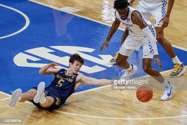 Cormac Ryan of the Notre Dame Fighting Irish reaches for the loose ball as c of the Kentucky Wildcats defends during the second half at Rupp Arena on...