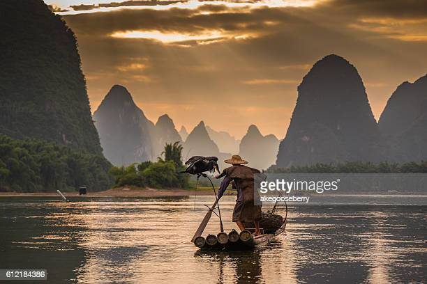 Cormorant and fisherman at dawn on the Li River, Guilin, Yangshou, Guangxi Province, China, Asia