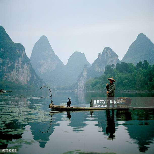 A cormorant Fisherman on the River Li near Guilin The River Li is famous for its unique scenery the kurst peaks the famous lichencovered monoliths...