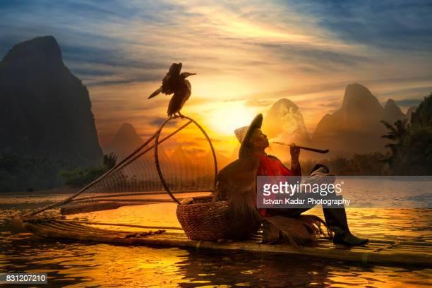 Cormorant Fisherman Smoking Pipe at Sunset, Yangshuo China