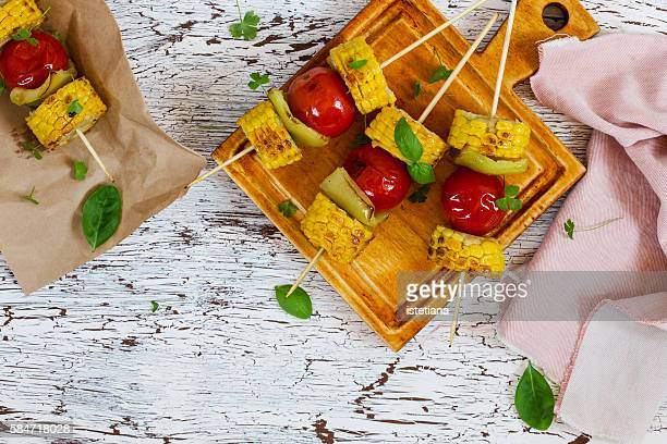 Corn and tomato veggie skewers, healthy vegetarian side dish on wooden rustic board viewed from above