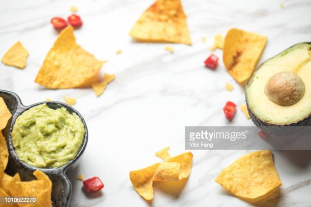 Corn chips served with guacamole on table