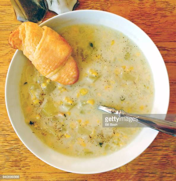 Corn chowder in a white bowl with bread roll and spoon - salt and pepper