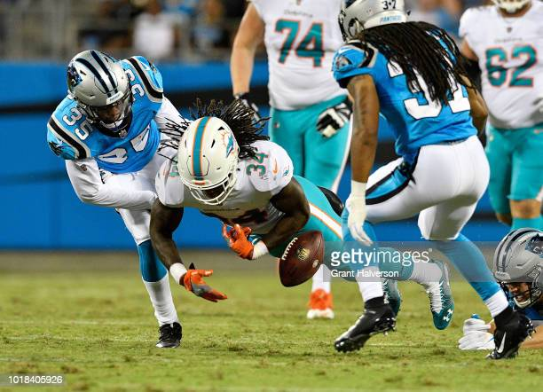 Corn Elder of the Carolina Panthers forces a fumble against Senorise Perry of the Miami Dolphins in the second quarter during the game at Bank of...