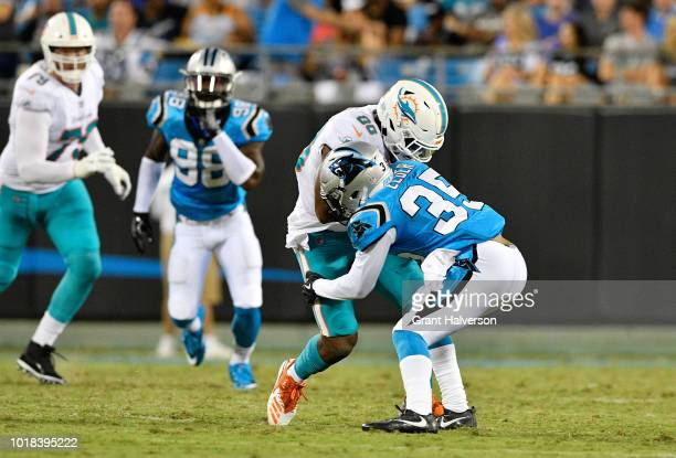 Corn Elder of the Carolina Panthers tackles Reshad Jones of the Miami Dolphins in the second quarter during the game at Bank of America Stadium on...