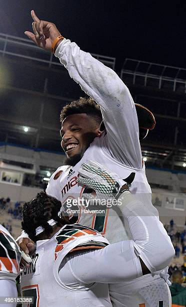 Corn Elder of the Miami Hurricanes celebrates with teammates after scoring the game-winning touchdown against the Duke Blue Devils during their game...