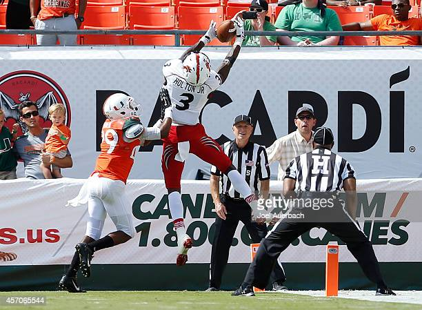 Corn Elder of the Miami Hurricanes prevents Johnny Holton of the Cincinnati Bearcats from catching the ball for a touchdown during fourth quarter...