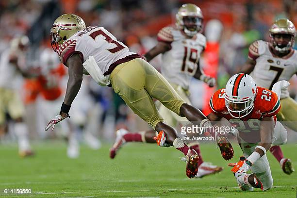 Corn Elder of the Miami Hurricanes tackles Jesus Wilson of the Florida State Seminoles on October 8, 2016 at Hard Rock Stadium in Miami Gardens,...