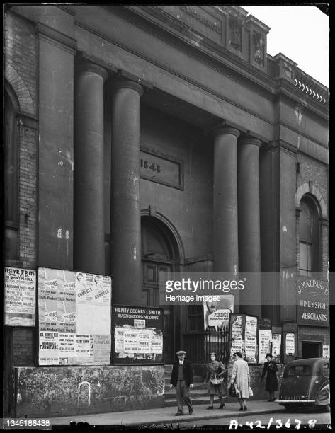 Corn Exchange, Angel Street, Worcester, Worcestershire, 1942. The entrance to the Corn Exchange adorned with advertisments and promotional posters....