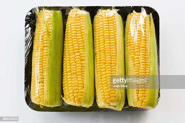 Corn on the cob wrapped in plastic