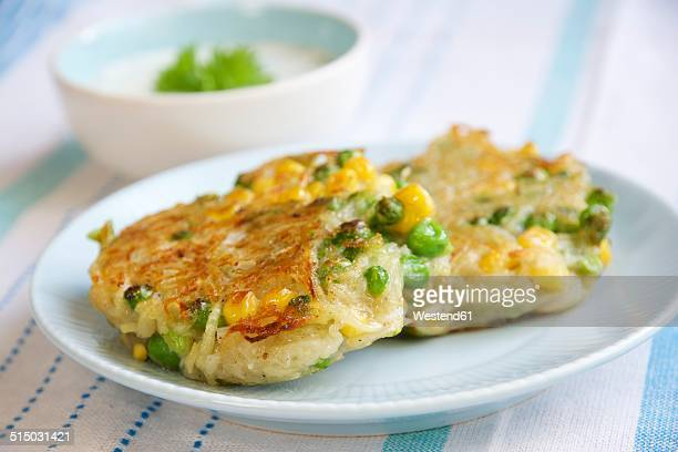 corn, pea and potato patties with herbed soy yogurt sauce - fritter stock photos and pictures