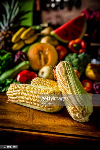 Corn with assorted organic tropical fruits and vegetables in a rustic kitchen background. Natural lighting