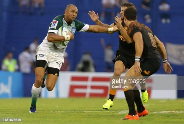 Cornal Hendricks of Bulls hands off Javier Ortega Desio of Jaguares during the Super Rugby Rd 2 match between Jaguares and Bulls at Jose Amalfitani...