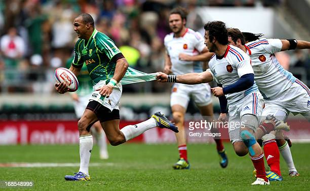 Cornal Hendricks of South Africa attempts to break free from the tackle of Vincent Deniau of France during the Marriottt London Sevens Day One at...