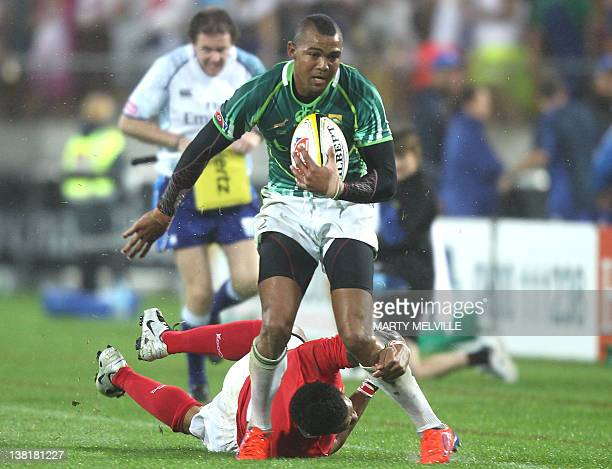 Cornal Hendricks of South Africa is tackled by Kilifi Latu of Tonga during the plate final at the Rugby Sevens tournament in Wellington on February 4...