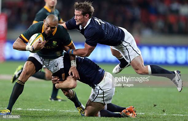 Cornal Hendricks of South Africa on attack as he is tackled during the Incoming Tour match between South Africa and Scotland at Nelson Mandela Bay...