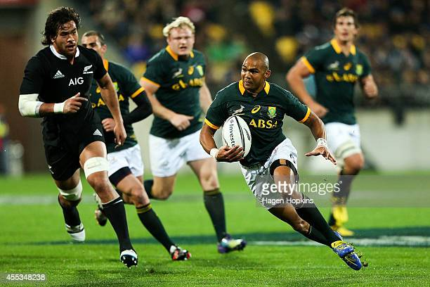Cornal Hendricks of the Springboks makes a break on his way to scoring a try during The Rugby Championship match between the New Zealand All Blacks...