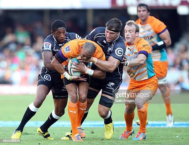 Cornal Hendricks of the Toyota Cheetahs tackled by Tonderai Chavhanga and Willem Alberts of the Cell C Sharks during the Super Rugby match between...
