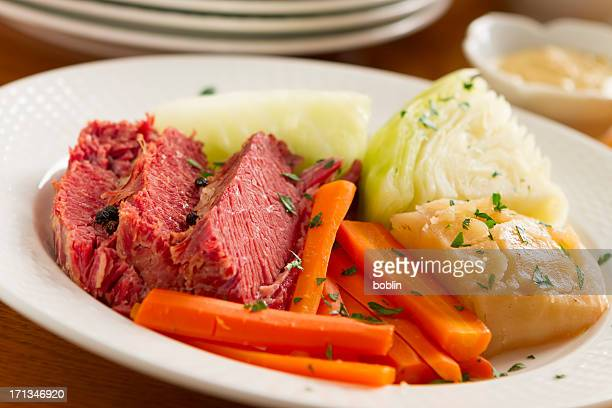 Corned beef, carrots, and onion on a white plate