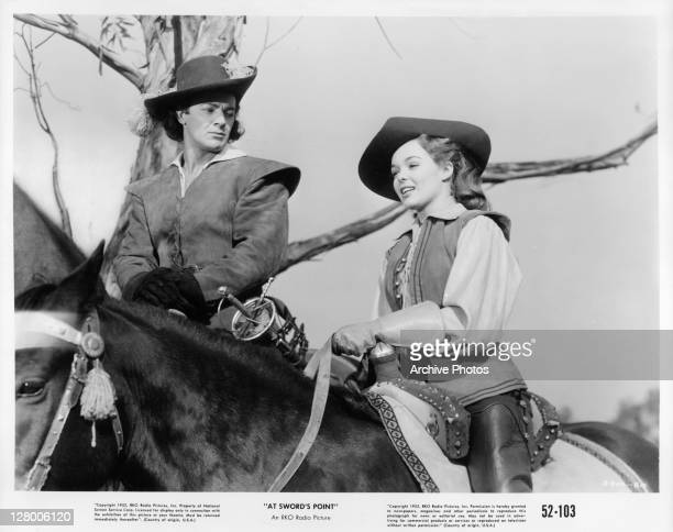 Cornel Wilde and an unidentified actress on horseback in a scene from the film 'At Sword's Point' 1952