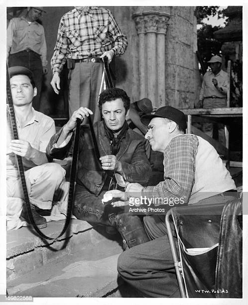 Cornel Wilde appraises film clips in between scenes from the film 'Passion' 1954