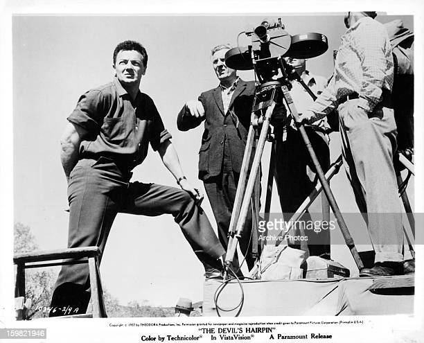 Cornel Wilde standing next to cameras in between scenes from the film 'The Devil's Hairpin' 1957