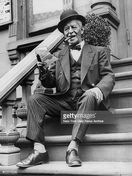 Cornelius Hughes proudly holds up his winning sweepstake ticket on the front stoop of his home in New York