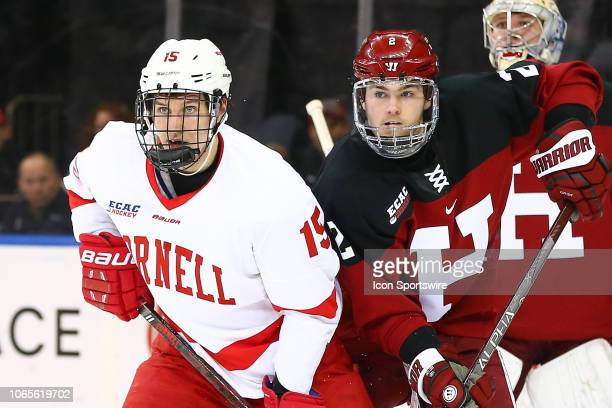 Cornell Big Red forward Max Andreev battles Harvard Crimson defenseman Reilly Walsh during the 2018 Frozen Apple College Hockey game between the...