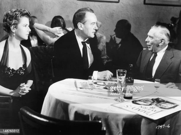 Cornell Borchers and George Sanders are invited by Ray Collins to join him at his table in a scene from the film 'Never Say Goodbye', 1956.