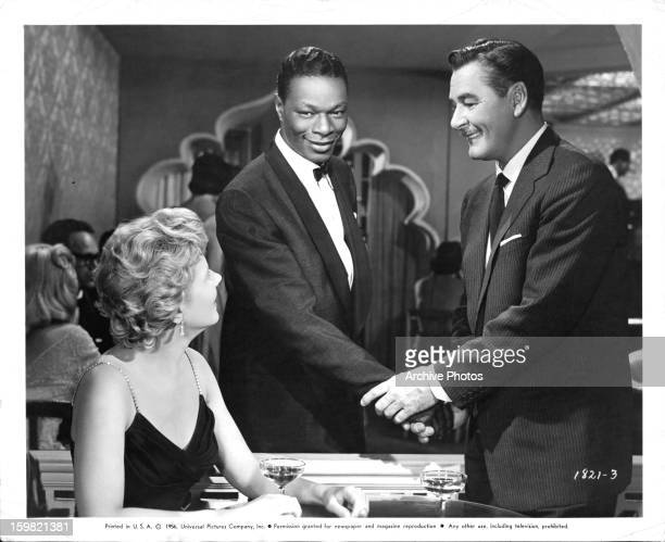 Cornell Borchers looking up at Nat 'King' Cole and Errol Flynn in a scene from the film 'Istanbul', 1957.