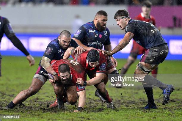 Cornell Du Preez of Edinburgh is tackled by Zurabi Zhvania of Stade Francais during the European Rugby Challenge Cup match between Stade Francais and...