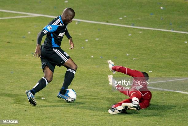 Cornell Glen of the San Jose Earthquakes dribbles the ball around the reach of goalkeeper Bouna Coundoul of the New York Red Bulls before kicking the...