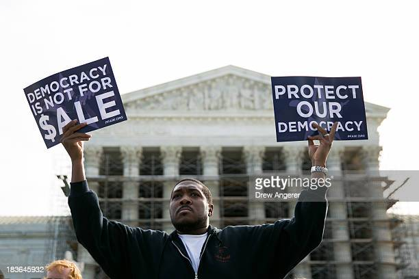 Cornell Woolridge holds signs as he rallies against money in politics at the Supreme Court in Washington on October 8 2013 in Washington DC On...