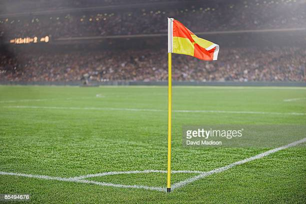 Corner flag on soccer field with spectators.