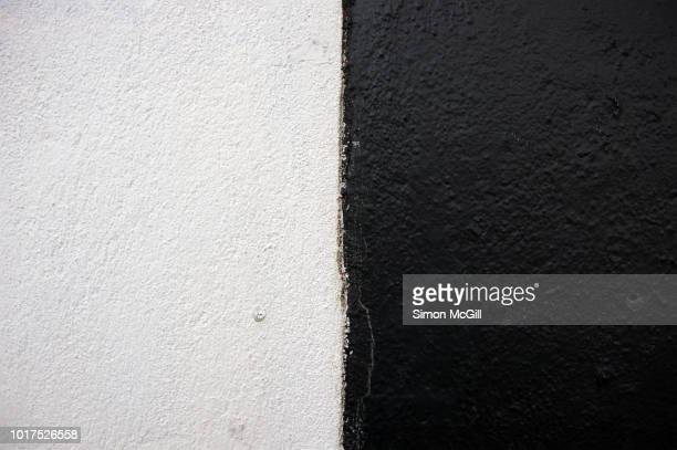 Corner of a cement-sheeting clad building exterior wall painted in black and white