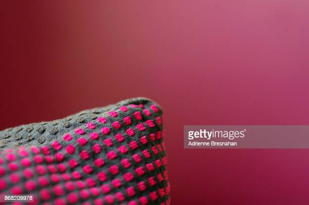 Corner of a Patterned Pillow Against Dark Pink Background