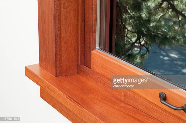 Corner of a window sill with a brown wooden frame