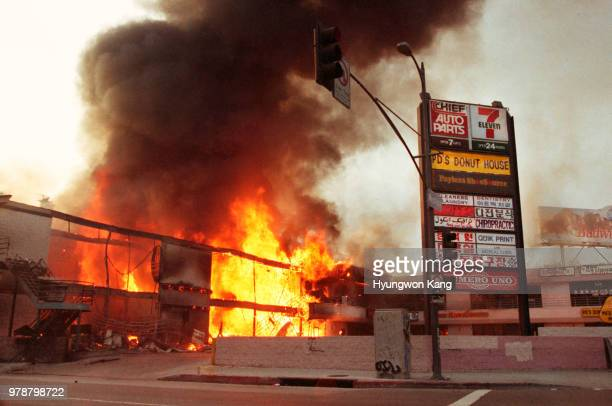 A corner shopping center at the intersection of Western Avenue 6th Street is fully engulfed in flames as it is left burning out of control in...