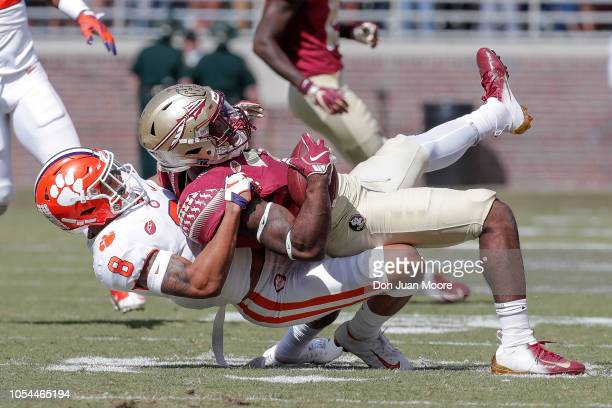 Cornerback A J Terrell of the Clemson Tigers brings down Runningback Cam Akers of the Florida State Seminoles during the game at Doak Campbell...